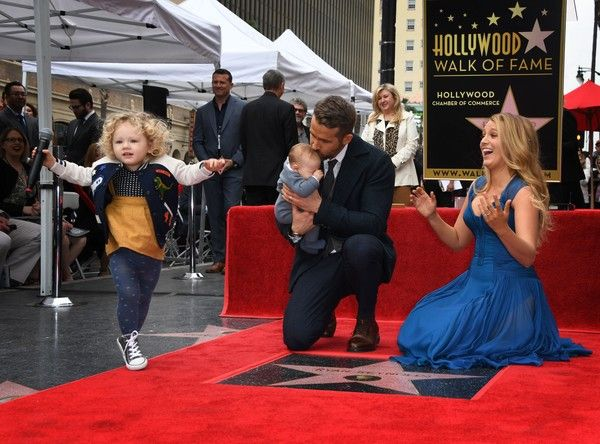Blake Lively Photos Photos - Actor Ryan Reynolds (C) kisses his unnamed new baby as his wife Blake Lively and daughter James look on during the Deadpool actors Hollywood Walk of Fame ceremony in Hollywood, California on December 15, 2016. / AFP / Mark RALSTON - Ryan Reynolds Honored With Star On The Hollywood Walk Of Fame