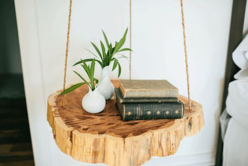 Tree trunk slices hung with twine as bedside tables.: