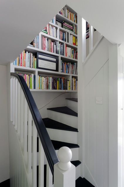 Farmhouse Staircase by Inspired Design Ltd This staircase had to be replaced, so O'Mara built in a wall-to-wall bookcase, both as a storage solution and to create a colorful feature in an otherwise dead space. She used Farrow & Ball Railings paint on the steps to highlight the geometric shapes.