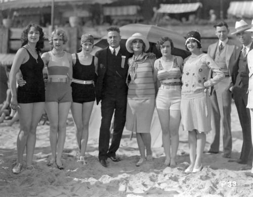 Carole Lombard, fifth from left, taken sometime in 1928 during work on one of Mack Sennett's comedy shorts. Lombard apparently wasn't scheduled to appear in swimwear that day, as she's wearing a horizontally-striped sweater and skirt. Sennett himself is at far right, in a white hat. Others posing with Carole are, from left, Kathryn Stanley, Leota Winters, Madeline Hurlock, visitor to the set L.M. Cobbs, Nancy Cornelius and Marie Pergain. We hope the person who wrote on the back of this photo…