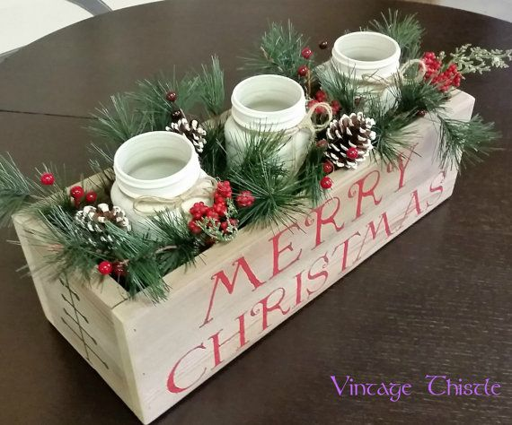 Rustic wooden planter box hand made from reclaimed cedar. The planter box has been whitewashed and stenciled with a holiday greeting and primitive Christmas tree. Three white painted Atlas Mason glass jars and greenery are tucked inside the planter box to make a beautiful addition to your holiday table.  The wooden planter box measures approximately 18 long by 5.5 tall (not including jars) by 6.5 wide.  This set includes: one 18 long cedar planter box whitewashed and waxed three painted…