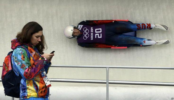 Natalja Khoreva dari Rusia pada latihan olahraga luging putri sementara seorang tenaga sukarela melewatinya di Krasnaya Polyana, Rusia (9/2). (AP/Dita Alangkara)
