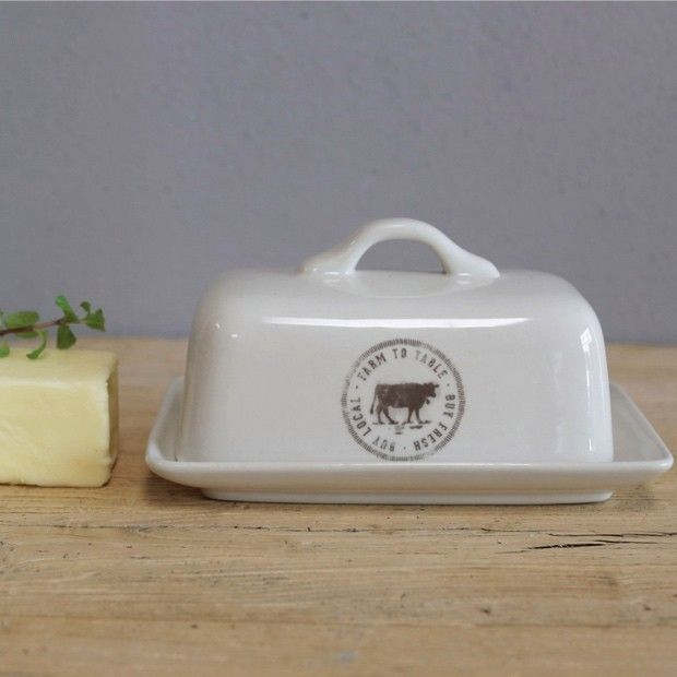 """Farm to Table Stoneware Butter Dish Farm to Table Stoneware Butter Dish features a farm friendly reminder to """"buy fresh, buy local."""" Nothing is better than farm to table products! A simple white stoneware butter dish printed with a cow and words to live by will be a delightful addition to your farmhouse wares."""