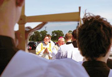 Bishop David Malloy (center), Deacon Gregory Urban of St. Mary of the Assumption Parish in Maple Park and altar servers are framed by other altar boys, one holding a crucifix, at the dedication of the new St. Gall Church in Elburn on June 11. Read more in The Observer June 16, 2017.