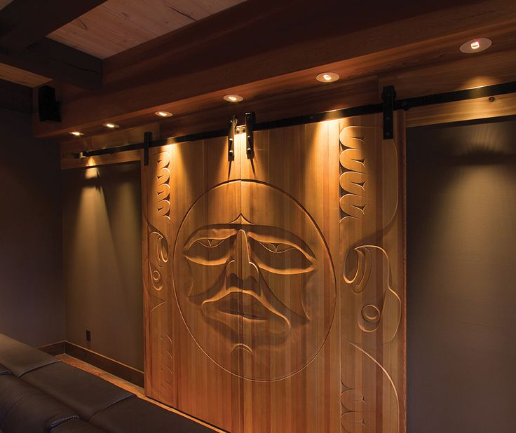Completed custom carved cedar doors showing images of the Sun flanked by two eagles.  By George Hemeon