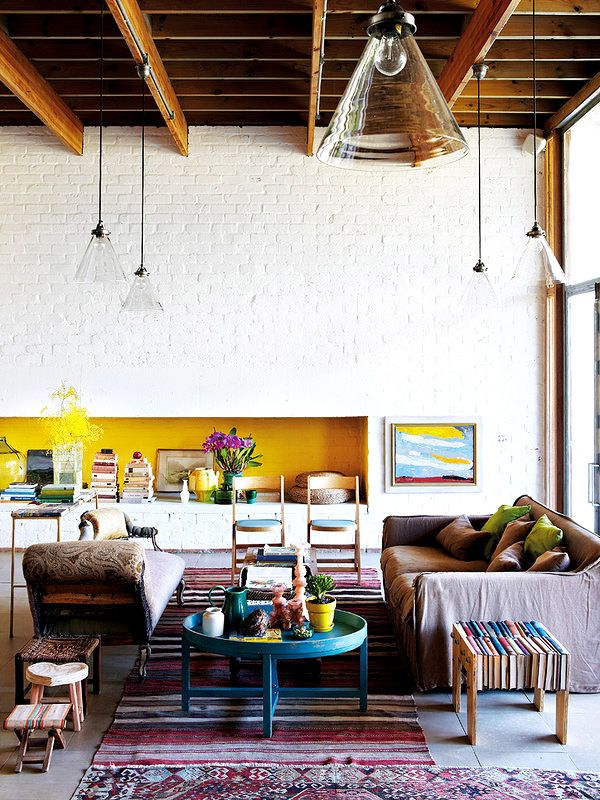 Living space with wood ceiling, white brick walls, glass light fixtures, colorful striped rug, blue coffee table, wood chairs, brown couch, antique stools, and plants