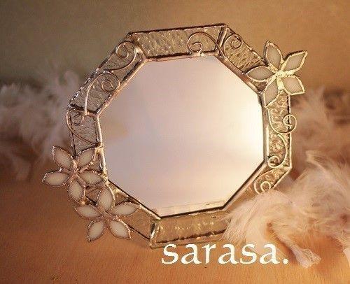 ステンドグラスで制作した八角形の鏡 クリアの表情あるガラスに白いお花をあしらい、ワイヤーでアレンジ♪ フックが上部についていますので壁にかけて~(*´▽`*)八角形の鏡は風水で縁起がいいものとされ好まれています♪*** 風水で鏡は「水」をあらわし気の向きを変えたりするもの だからこそ置き場所を間違えずに正しく飾れば便利なアイテム気の出入り口であるとされる玄関に置くことで良い気の流れを作用させそこへ暮らす人たちへ、豊か�
