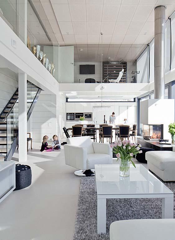 Oleskelutiloista on avoin yhteys keittiöön ja alhaalta yläkertaan. Salolaisen RMJ Saksmanin Kuura-sarjan sohvapöytä ja tv-taso ovat Boulevard Furnituresta. | Moderni kotisatama | Koti ja keittiö