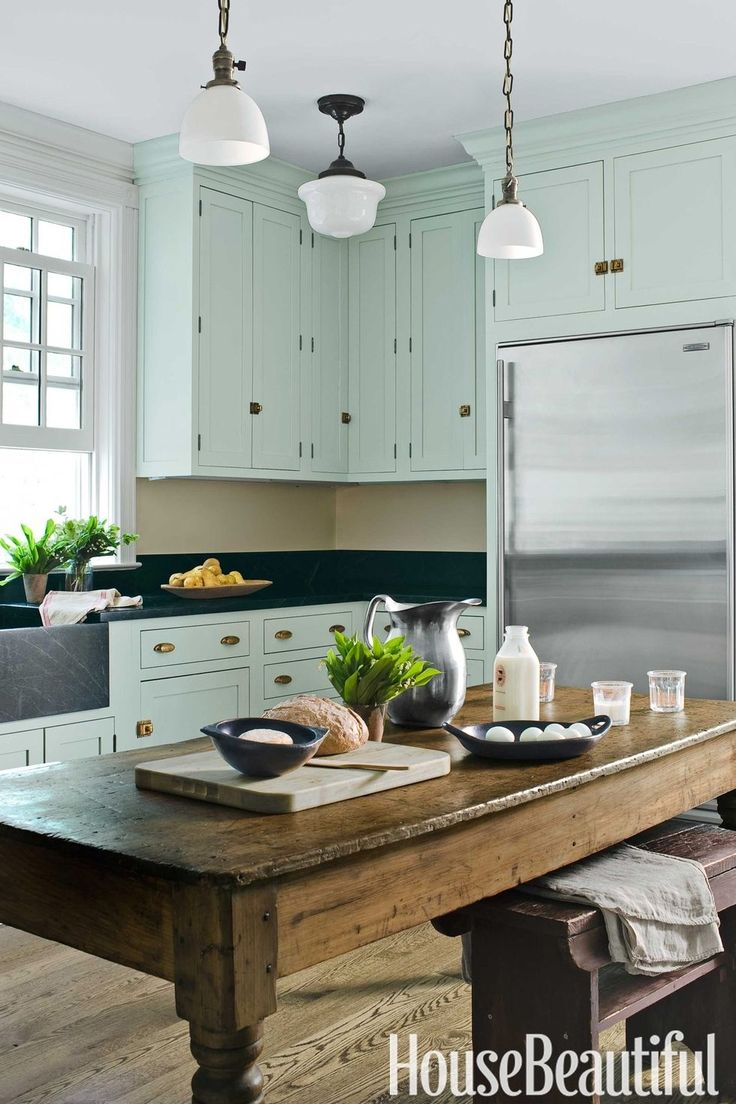 Shaker-style cabinets in a color between mint and aqua give a fresh yet old-fashioned look in a Mount Kisco, New York, farmhouse-style kitchen. See more green paint colors for every room at HouseBeautiful.com.