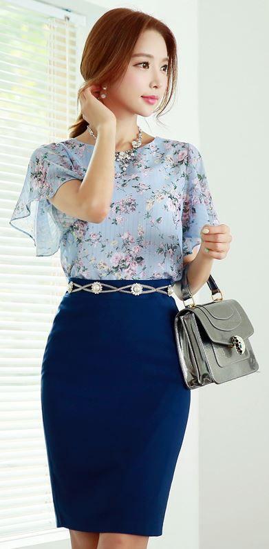 Blusa tecido leve, florida, azul claro, mangas esvoaçantes, combinada com saia lápis de cintura alta, cinto prata e bolsa de mão.