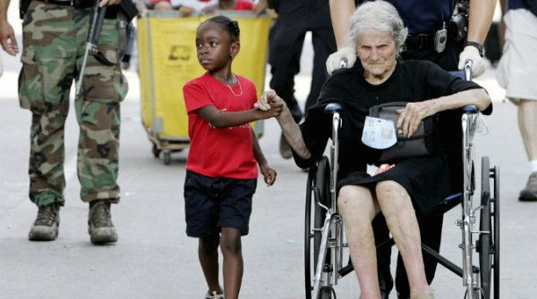 Per mano Un ragazzino conforta una donna anziana che ha perso tutto nell'uragano Katrina (Credits: AP / Eric Gay)