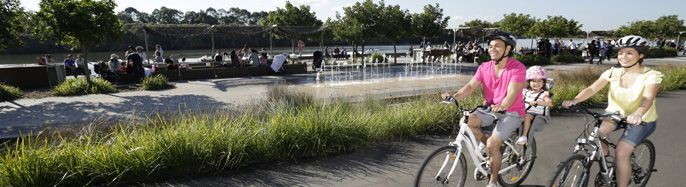 Family riding bikes along river at Blaxland Riverside Park ... Boasts biggest playground / free water park in NSW.