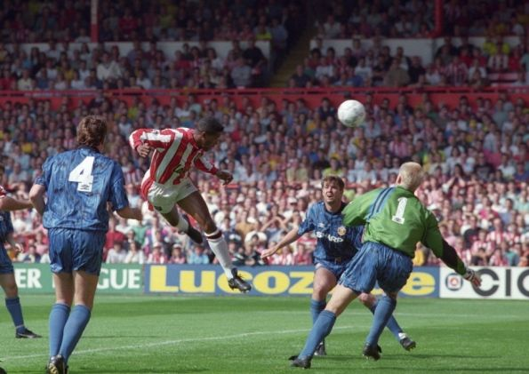 Sheffield United's Brian Deane sneaks in between Steve Bruce and Gary Pallister to nod home past Peter Schmeichel and score the first ever Premier League goal against Manchester United at Brammall Lane