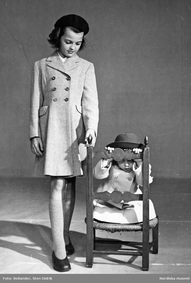 Två barn vid en stol. Flickan till vänster är klädd i dubbelknäppt kappa, basker, knästrumpor och skor. Barnet på stolen, i kappa och hatt. Fotograf: Sten Didrik Bellander, ca 1950-1955