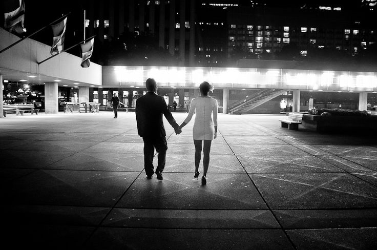 """Couple walking through Nathan's Phillip Square.   The lights in the background illustrate a poem """"The rose without why"""" by Johann Scheffler and exhibited by Boris Achour.    """"The rose is without 'why'; it blooms simply because it blooms. It pays no attention to itself, nor does it ask whether anyone sees it."""""""
