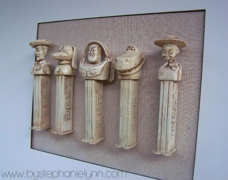Pez wall art....Toy Story Pez immortalized...spray paint, antiqued, mounted, hung...very cool idea...pick your favorite Pez series to immortalize...this works for grownup funky art, too!