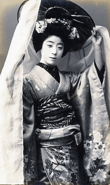 Geiko Yachiyo dressed for an Odori (Dance), holding a hat from the Heian Period.  Yachiyo (b.1887 - d.1924) was a famous Geiko (Geisha) from Osaka, known for her elegance and her lovely personality. People were said to weep with joy at the sight of her dancing. She became a Maiko (Apprentice Geisha) at the age of thirteen and left the profession to marry the artist Suga Tatehiko (b.1878 - d.1963) at the age of 29, but died at 36 from an inflammation of the kidneys.