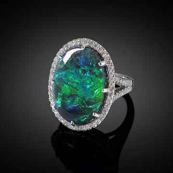 A kaleidoscope of colors is exhibited in this striking 16.44-carat black opal, which hails from the famed Lightning Ridge Mine in Australia. Brilliant white diamonds, weighing 1.43 total carats, add exceptional sparkle to this extraordinary platinum ring ~ M.S. Rau Antiques #opalsaustralia