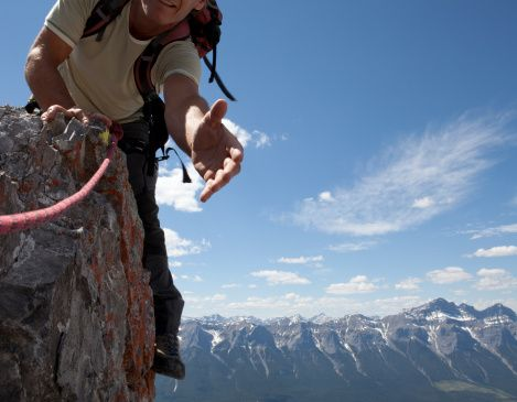 Stock Photo : Climber extends a helping hand to teammate, mtns
