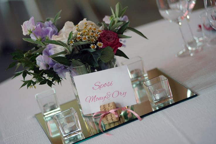 Anche il segnatavolo con i tappi di sughero e il centrotavola con i colori dal rosa antico, ciclamino e lilla seguono la tendenza countrychic di questo matrimonio