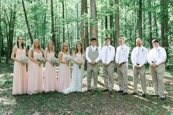The bridesmaids in long pink dresses stand with the bride, who wears a long lace strapless wedding dress. The groom and groomsmen wore khaki pants and patterned ties for this forest wedding.