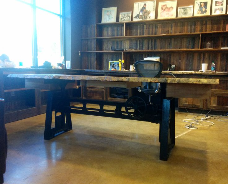 Custom table built by Southern Accents for McPhearson Oil. Table top created from salvaged wood. Table base is a salvaged industrial piece.
