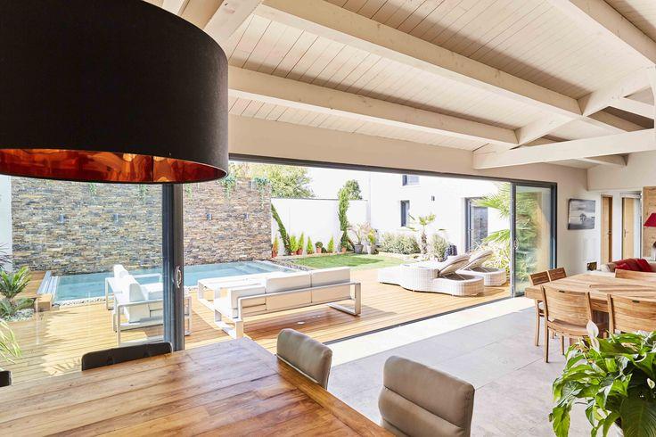 Une belle ouverture sur un jardin aménagé avec goût ! Une terrasse en bois autour d'une belle piscine.   #menuiserierideau