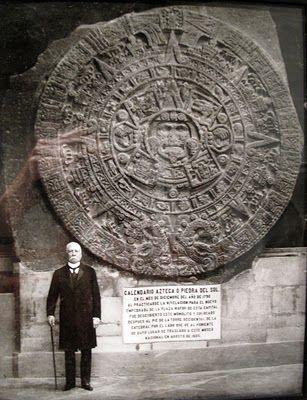 """Porfirio Díaz parado junto a la """"Piedra del Sol"""" que NO es calendario, es la representación de la cosmogonía mexica/azteca. En ella se narran la secuencia de la creación del hombre, el paso de las 5 eras de creación y destrucción de su mundo por las deidades creadoras y destructoras, Fue encontrada al hacer excavaciones el el área del zócalo capitalino, Pesa aproximadamente 24 toneladas. Se cree que originalmente estuvo policromada y tenía la función de círculo gladiatorio."""
