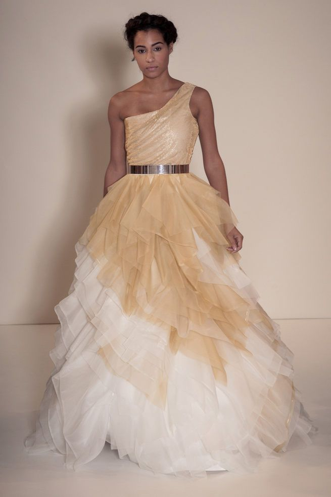 Asymmetrical off the shoulder wedding dress in gold and white with gold belt and layered tulle skirt. Della Giovanna Wedding Dresses