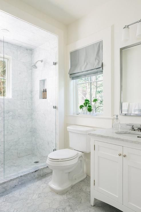 Large marble hex tiles lead to a white washstand topped with honed gray and white marble fitted with an oval sink tucked under a chrome framed mirror.