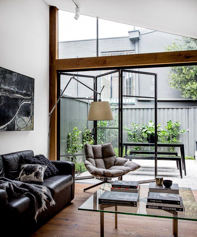 中庭の屋外リビングと全開口のガラスドアでつながる明るく開放的なリビング