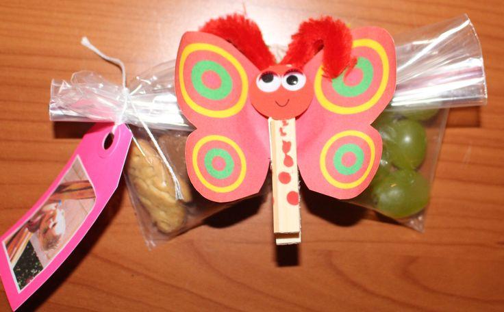 Voor de overgang van de rupsjes naar de vlinders een vlinder met in het zakje koekjes en druifjes. Tip deze goed gescheiden houden. Wasknijper door de jarige kleuter zelf beschilderd.