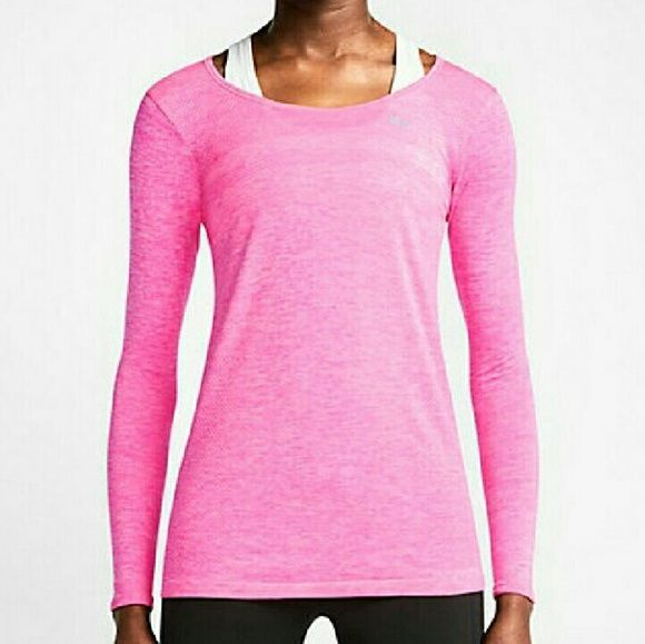 Nike Womens Running Top Nike Womens long sleeve running top. Hot pink with heathered look. Reflective swoosh logo on front. Reflective headphone loop at back neck. Thumb holes help keep sleeves in place in motion. Seamless body construction. Stretchy! Engineered pattern in fabric is slimming and helps keep you warm and dry. Dri-FIT technology.  The lightweight seamless construction, feels smooth against your skin to help reduce distractions as you move. Sits below the hip to reduce ride-up…