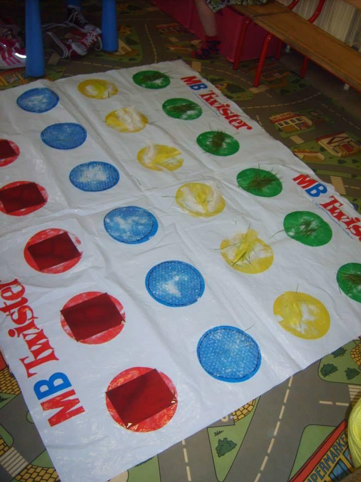 Voeltwister: rood schuurpapier, blauw noppenplastiek, gele pluimen en groen gras