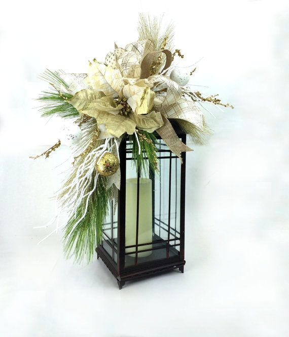 This Christmas Lantern Swag fits an 18-25 lantern and is in the colors of gold and white with poinsettia, ornaments and whimsical bow. This