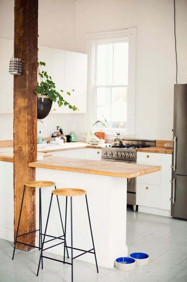 white cabinets with natural countertops. single rough beam. white, white, white. stools.