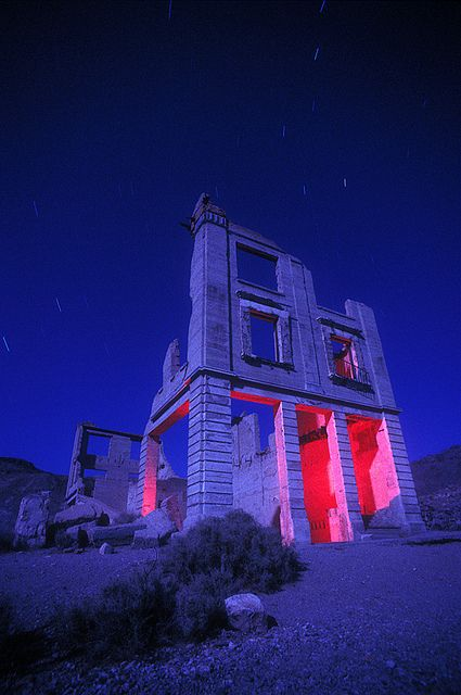 Founded in 1904, the town of Rhyolite, Nevada, peaked in 1907 with electric lights, water mains, telephones, newspapers, a hospital, a school, an opera house, and a stock exchange. By 1910, the mines played out and the town failed. By 1920, Rhyolite was totally abandoned, a classic American ghost town. Today, only a few shells of buildings remain, including this, the famous Cook Bank building.