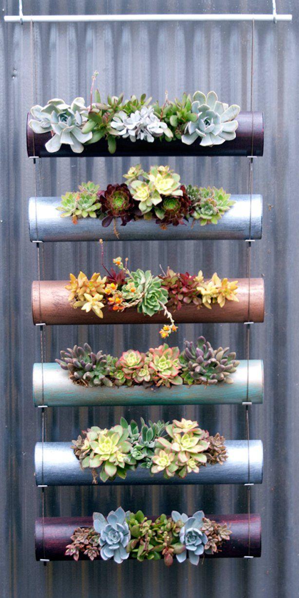 Reaproveite restos de tubos de PVC como recipientes para cultivar plantas e flores. Basta fazer um corte retangular para depositar o substrato e tampar as laterais para que se mantenha no lugar. Pinte os tubos com cores diferentes e prenda-os com cabos de aço.