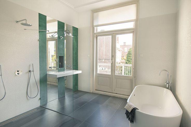Interior design by IJzersterk Interieurontwerp. Stadsvilla, Den Haag. Badkamer met hoge plafonds en hoge spiegels. Beton cire in petrolgroen, vrijstaand bad en dubbele inloopdouche.