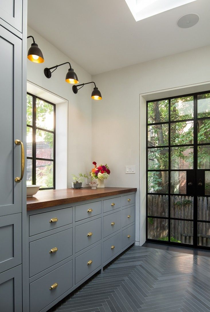 An existing window opening was enlarged to accommodate a new pair of steel French doors sourced from A&S Window Associates, based in Glendale, New York. The wall lights above the single-slab black walnut countertop are Navire Jib Sconces from LA-based Atelier de Troupe. The pantry door, with existing brass hardware, was original to the house.