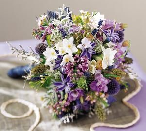 Lavender Cascade Bouquet  The Bride delights in Lavender stems, creatively cascading among lavender Lilacs and Larkspur. Delicate blooms in pink and white join in, alongside dried lavender Thistle, Wheat stems and Poppy Pods, for a natural touch.