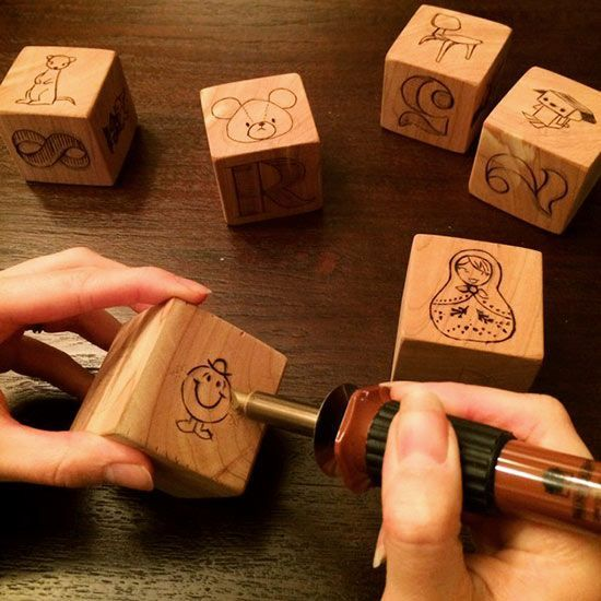 A baby's nursery isn't complete without aset of wooden blocks, but why buy when you can burn? The classic stacking toy becomes an instant heirloom when woodburned with favorite children's characters and eye-catching typography. Unless you're an expert at manipulating tiny curves with your woodburner tool, you might want to stick with simpler graphics and straight lines. Learn more at HelloBee./