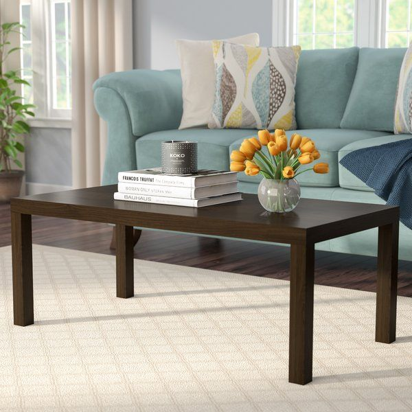 Lend your space a touch of streamlined contemporary style with this clean-cut coffee table. Made from solid wood, this dapper design showcases a rich dark brown finish, a simple rectangular silhouette, and four chunky square legs. Establish a transitional aesthetic in your open concept living room by rolling out a medallion-print area rug to define the space, then place this piece between a leather Lawson sofa with rolled arms and nailhead trim, and a glass-top console table topped with a…