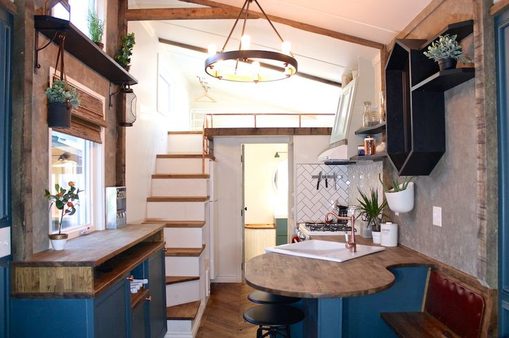 Digging the table seating situation. Stairs hold the refrigerator and other kitchen items.