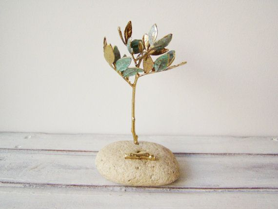 Schinus tree card holder is a set of real, schinus gold twigs on a natural stone. It is a cream coloured pebble that we randomly selected to make this