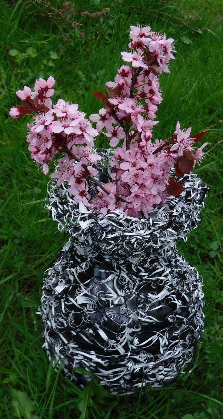 https://flic.kr/p/TpNtkE | Apr 1 2017 Phil's sculpture | This sculpture was made mostly from aluminum roof flashing that is black one side and white on the other. There is a small recycled glass bottle embedded in the top that holds water to keep the flowers fresh. I made a rough vase shape with recycled Styrofoam chunks covered with aluminum foil, then hot glued together. Some small rocks were inserted in the bottom for weight. Then I covered the shape with one cm strips of flashing…