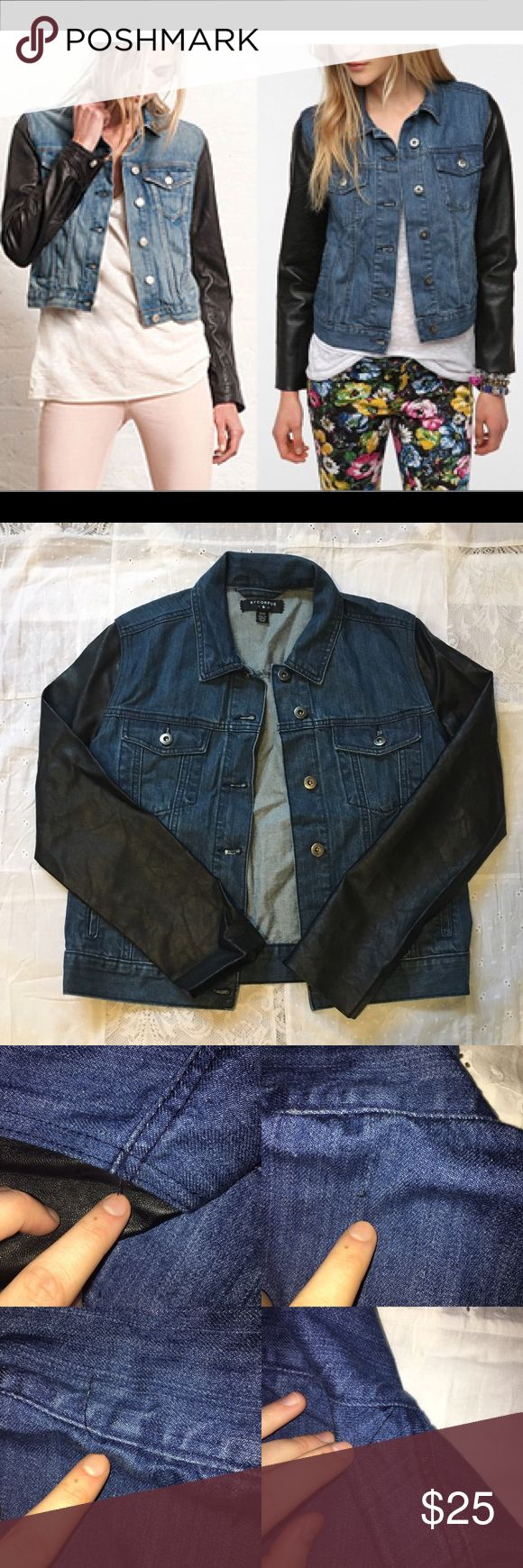 "BYCORPUS Dark Wash Denim Jacket Leather Sleeves Women's Dark Wash Denim Jacket with ""Leather"" Pleather Sleeves. Originally purchased from Urban Outfitters. * Size Medium * Great condition, wrinkles from storage * Jacket Body Materials: 100% cotton * Sleeve Materials: 100% polyester  * Pictured pulled strings located on back of collar of jacket and on the top part of sleeves  * Pockets * Pulled strings on the inside of jacket.                  *Dry clean only…"