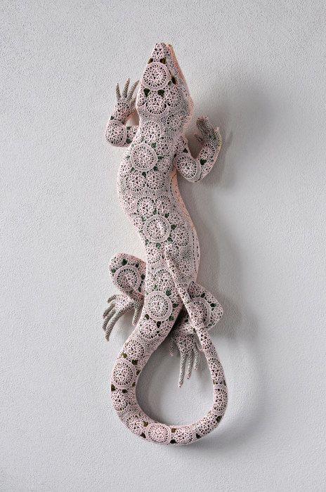 Керамическая ящерица, облаченная в изящные кружева.