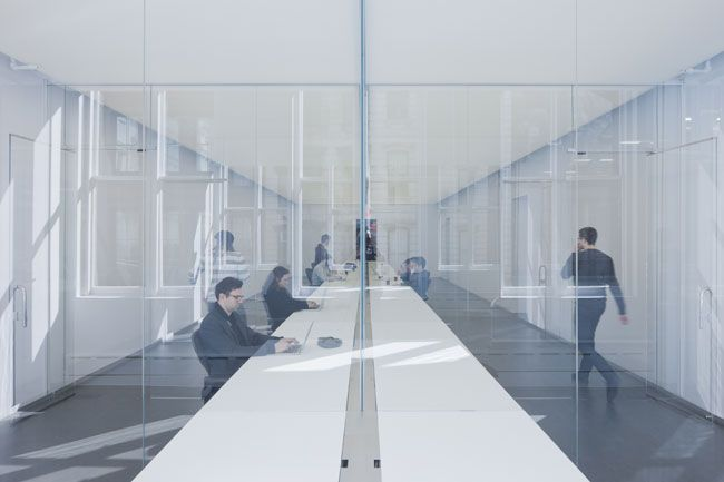 Two white tables topped with a seamless solid surface extend 65 feet down the length of both workspaces. At the end of one table in the inner workspace, two layers of glass divide offices for acoustic