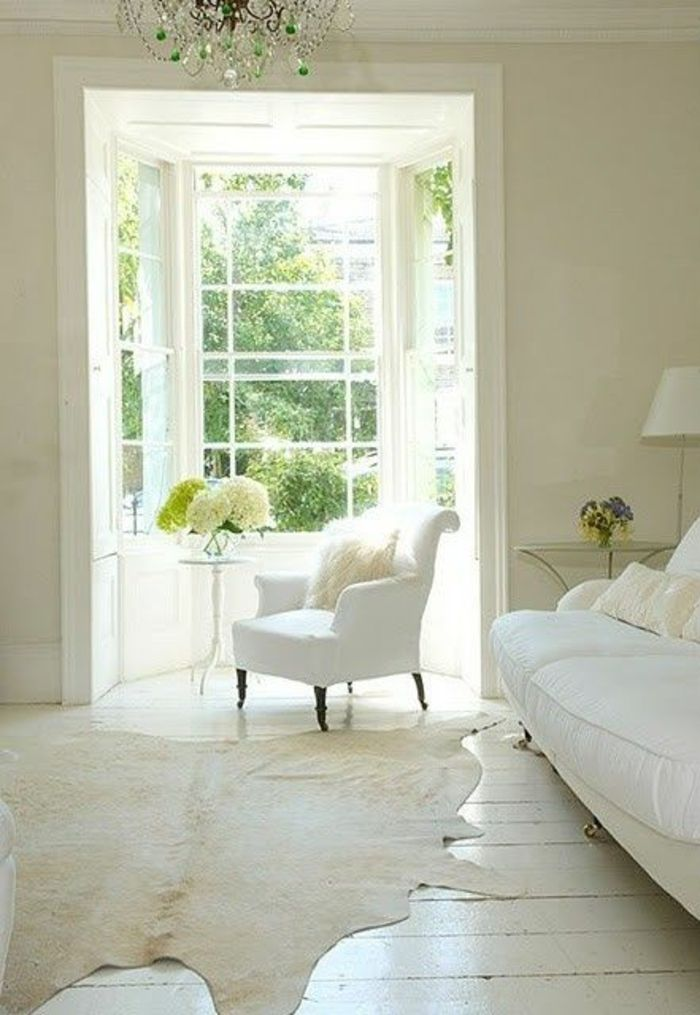 salon vaste, mur blancs, lustre baroque, tapis en peau de bete, fenetres grandes